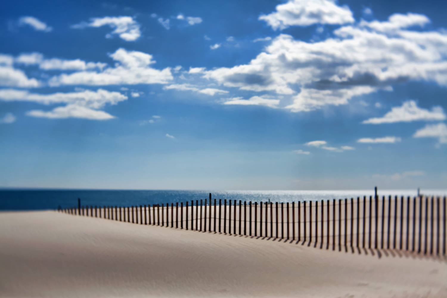 beach fence sand ocean blue sky white clouds selective focus Lensbaby featured photos of the week