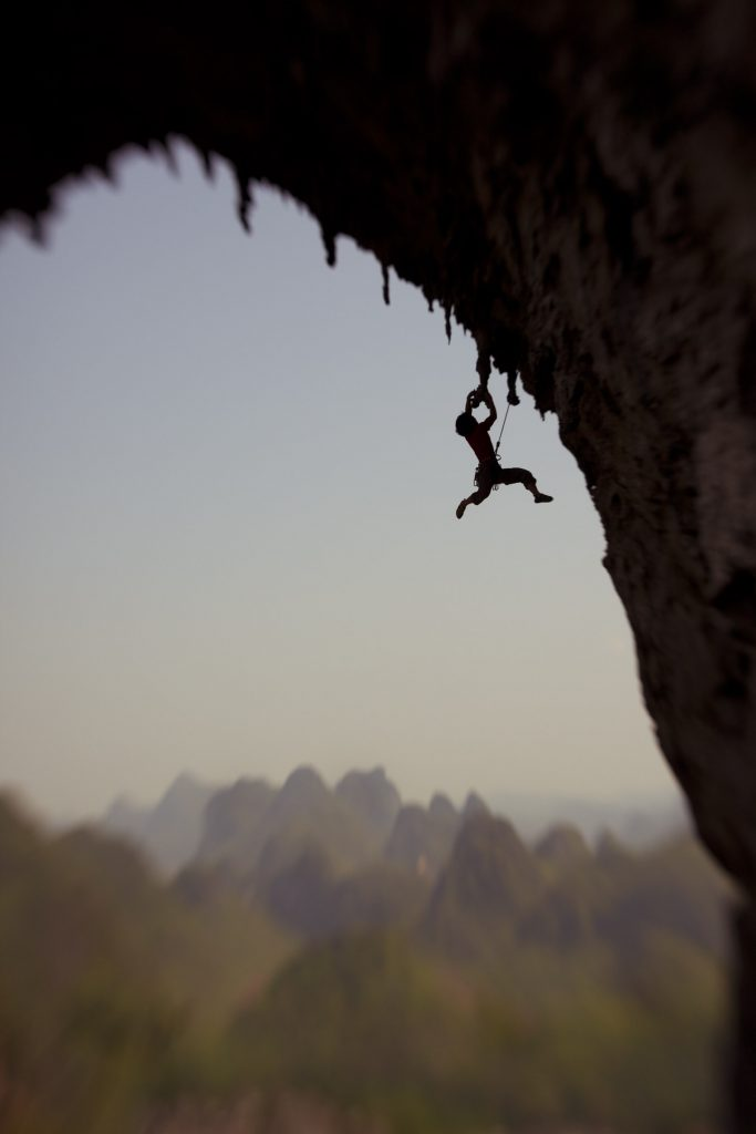 "Boone Speed with Original Lensbaby abond (liu yong bang) embarking on the ""Moon Hill Traverse"" --a potential traditional line utilizing tied-off tufas and slung threads as protection. The epic line will eventually traverse the entire arch. Moon Hill, Yangshuo, China."