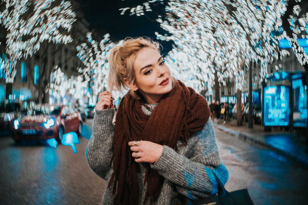 blonde woman with dark red scarf and gray sweater walks along a winter street white christmas lights Lensbaby Featured photos environmental portraits