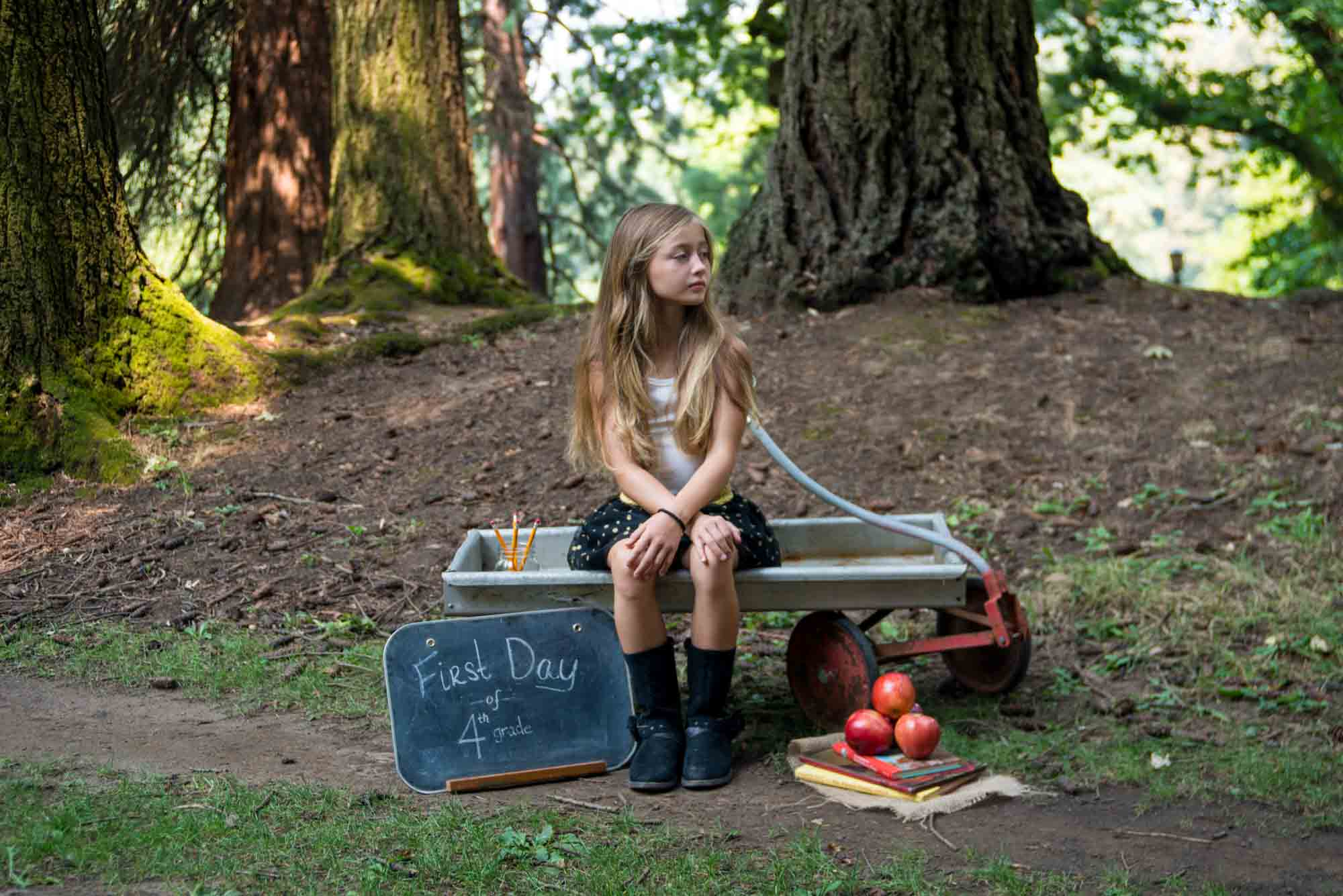 Back to school photo girl in park with wagon