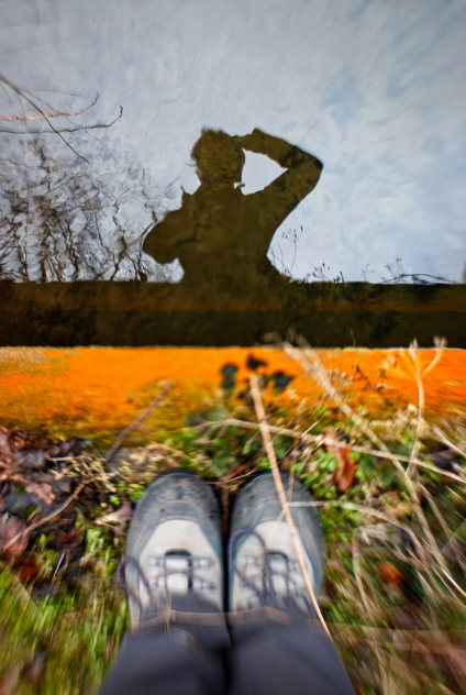 photographer taking self portrait in puddle feet water reflection orange flowers hiking boots Lensbaby featured photos