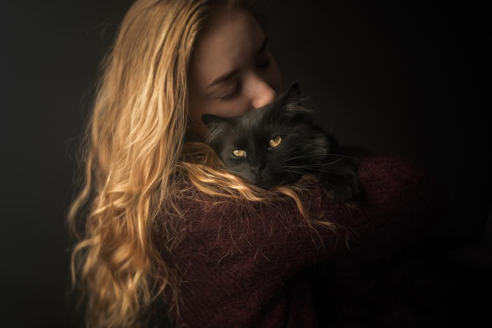 girl with blonde hair holding black cat with yellow eyes cuddling caroline jensen Lensbaby featured photos of the week
