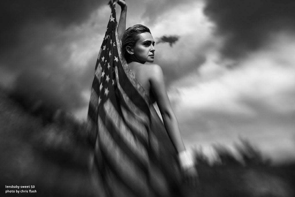 woman draped with an american flag in front of moody clouds black and white photography our passion is the imperfect