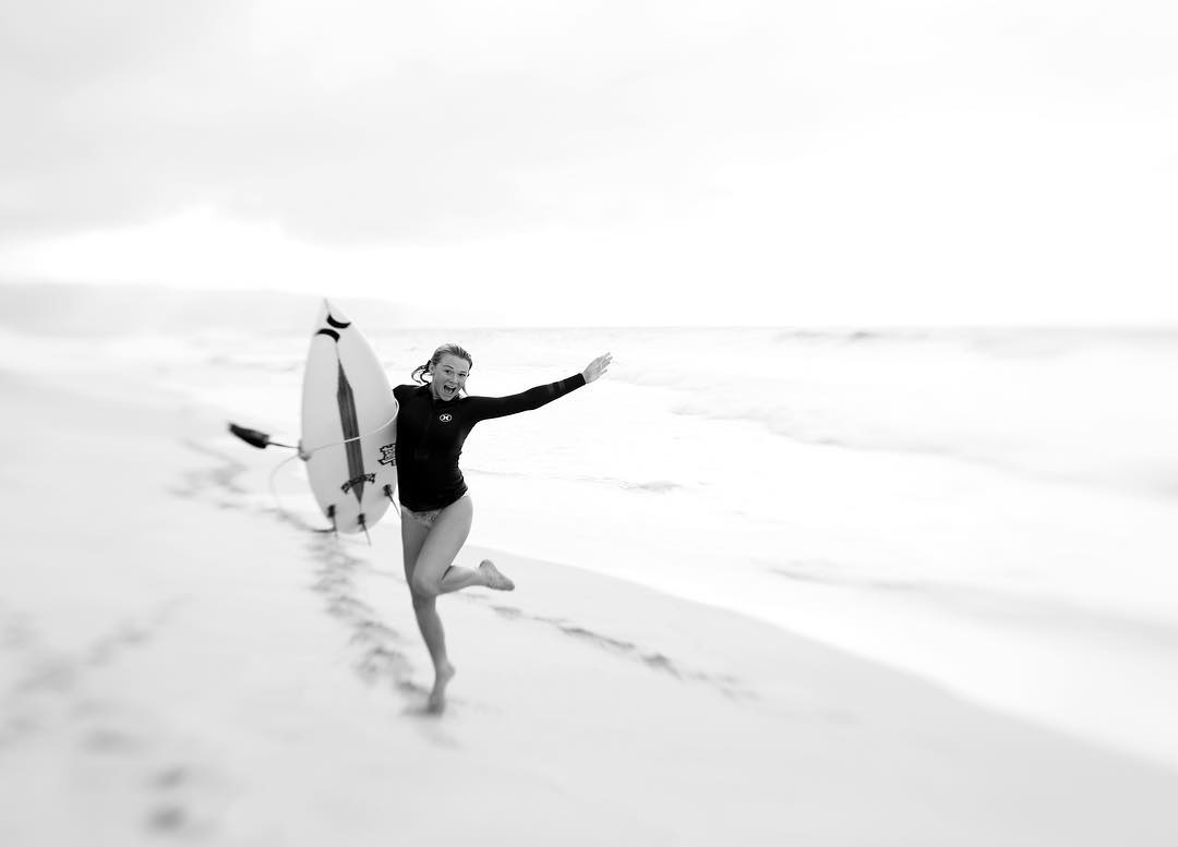 woman at the beach with a surfboard blond hair smile jumping featured photos of the week