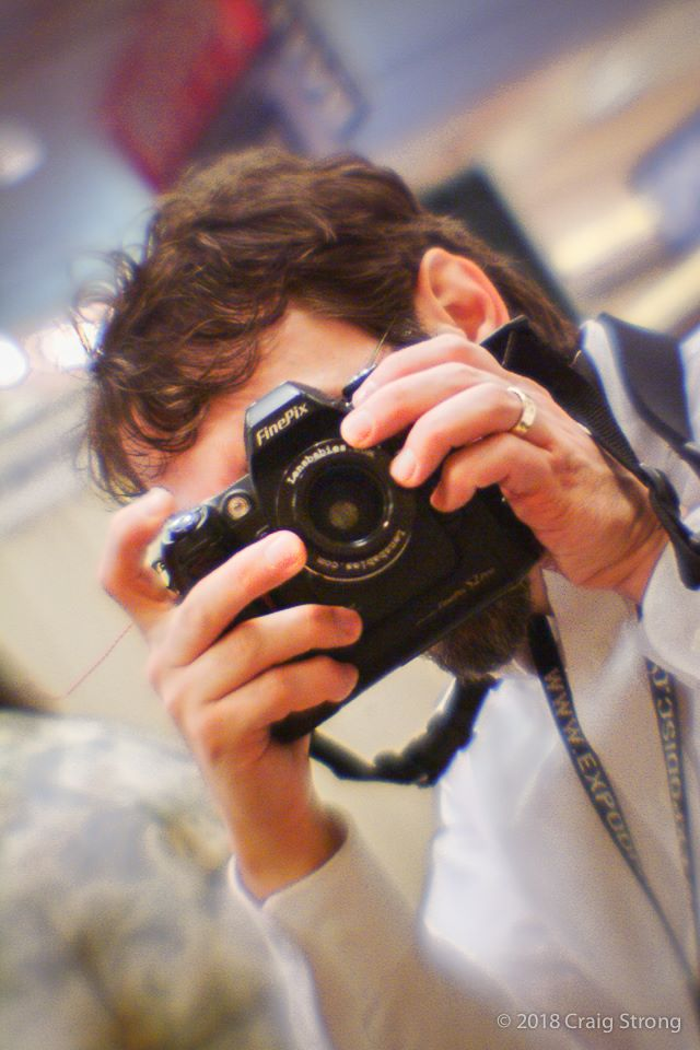man with brown hair white collared shirt taking a photo with a finepix camera lensbaby history
