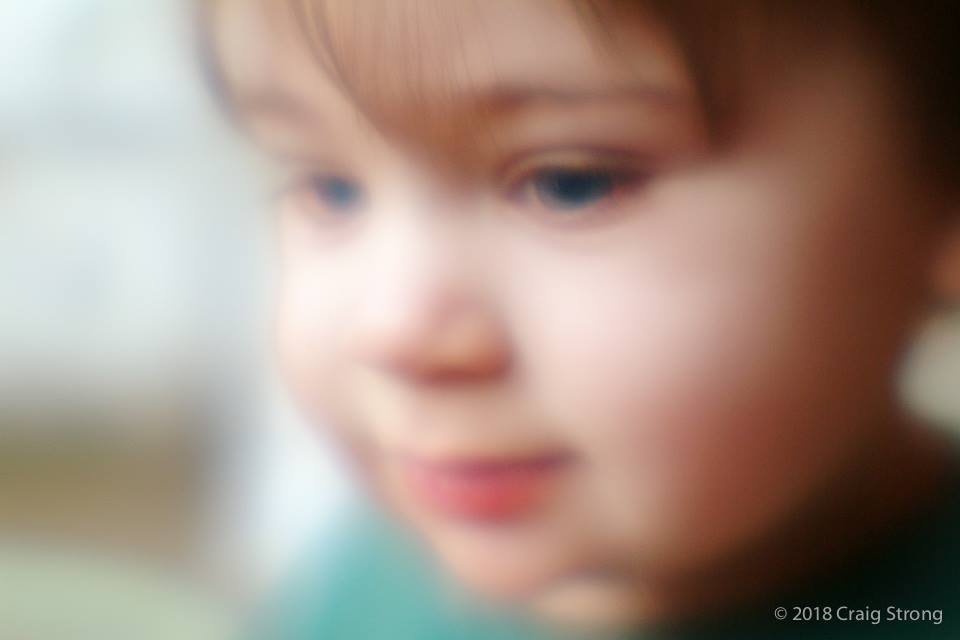 kid with red lips green shirt blue eyes portrait lensbaby history