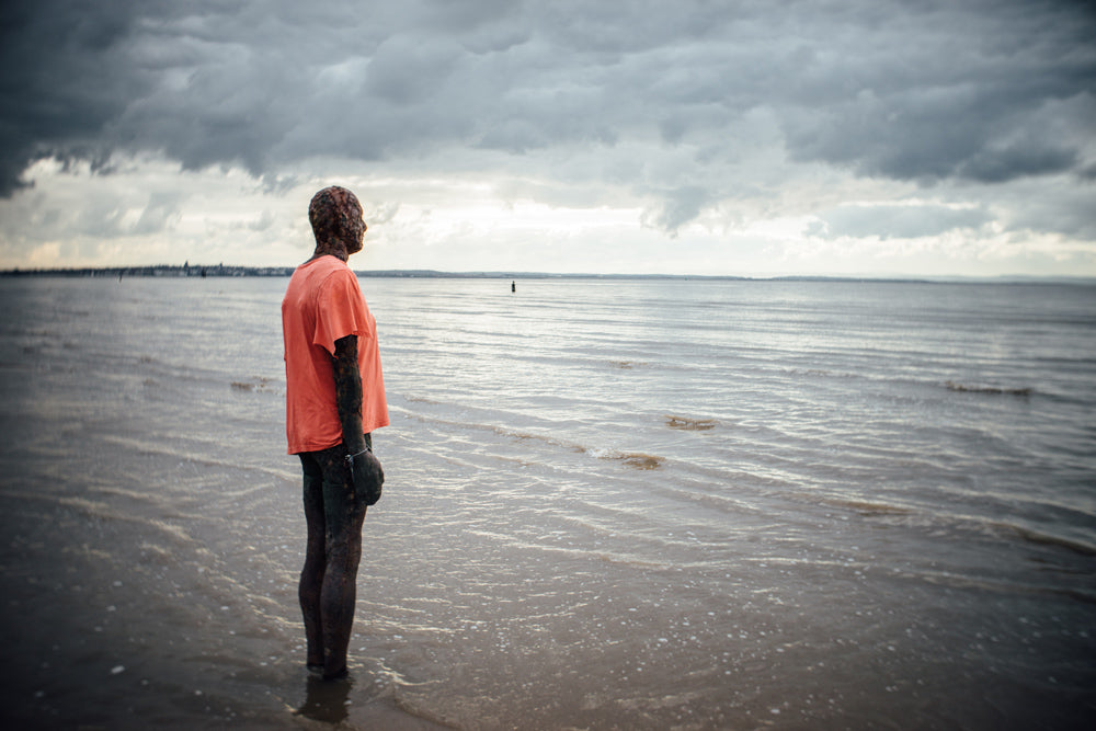 iron statue in orange t-shirt by the beach Anthony Gormley's Another Place UK Liverpool janet broughton Burnside 35