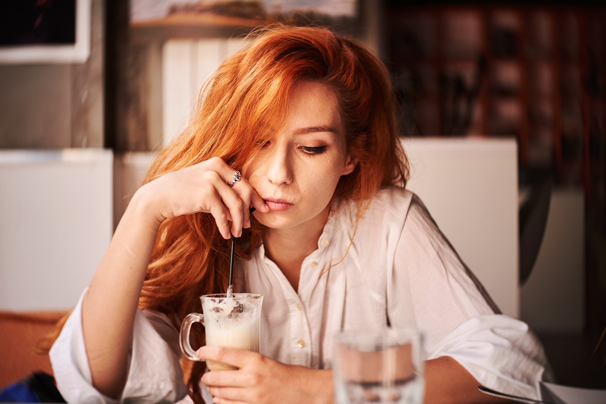 Woman with red hair drinking out of a straw at a diner