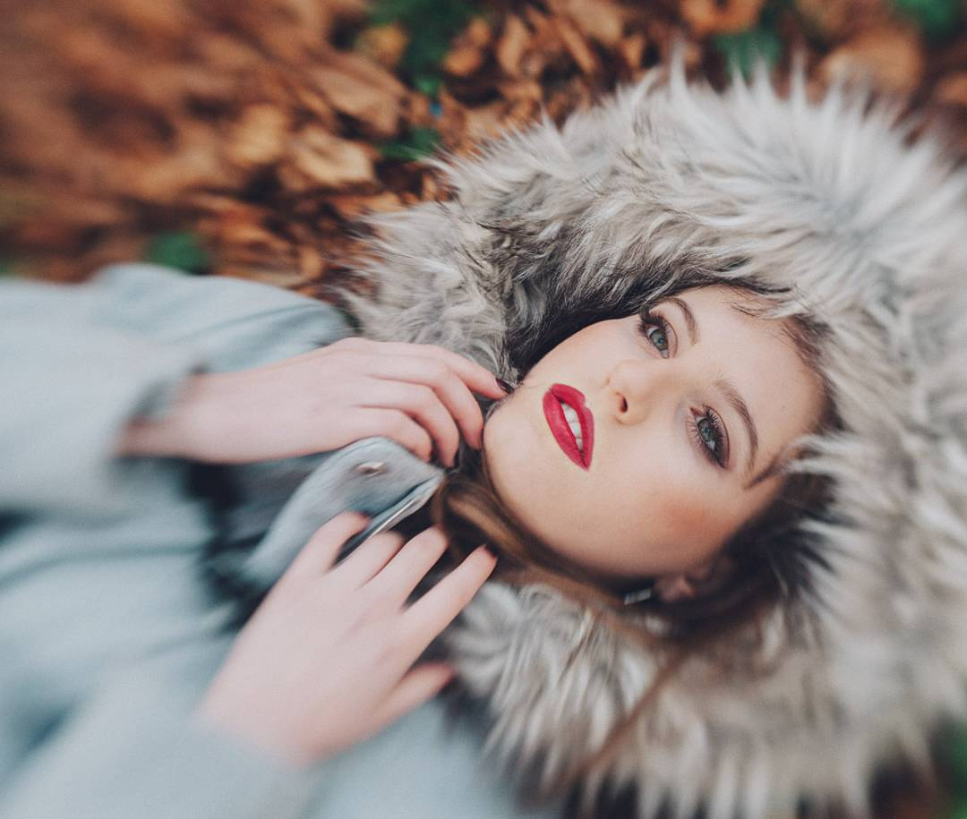 woman in fur coat with red lipstick lays in fall leaves featured photos of the week