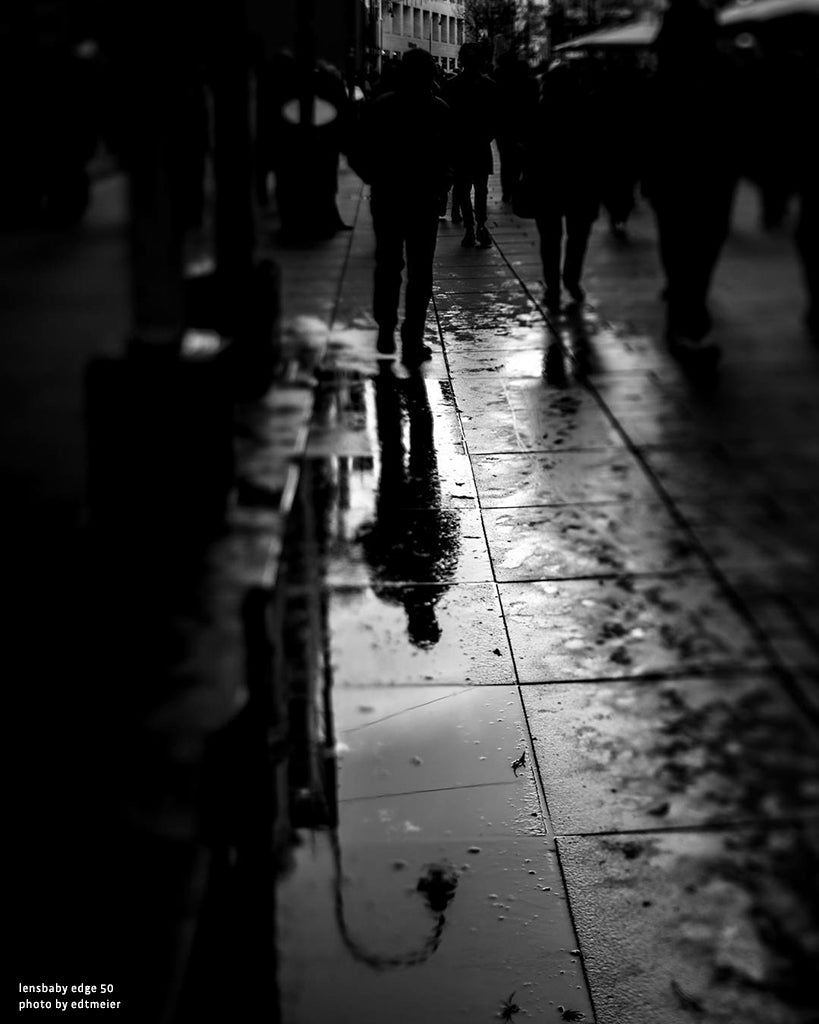 man's reflection in the street people walking city black and white photography our passion is the imperfect