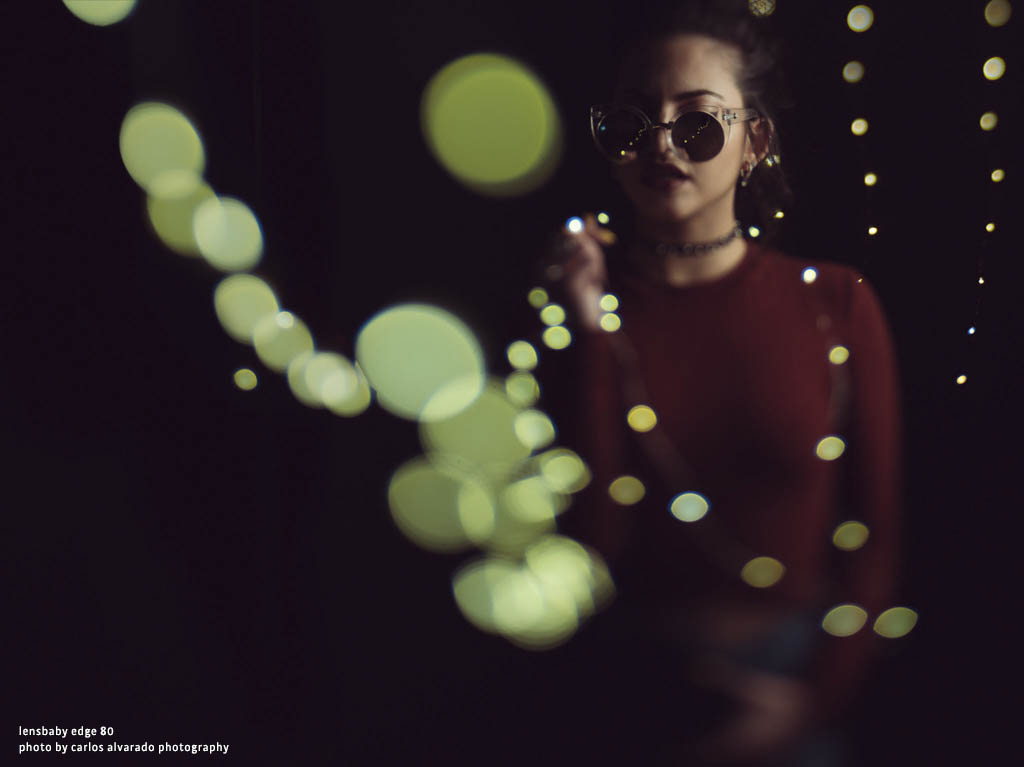 woman with round sunglasses and a red sweater surrounded by green light bokeh Lensbaby top 12 photos