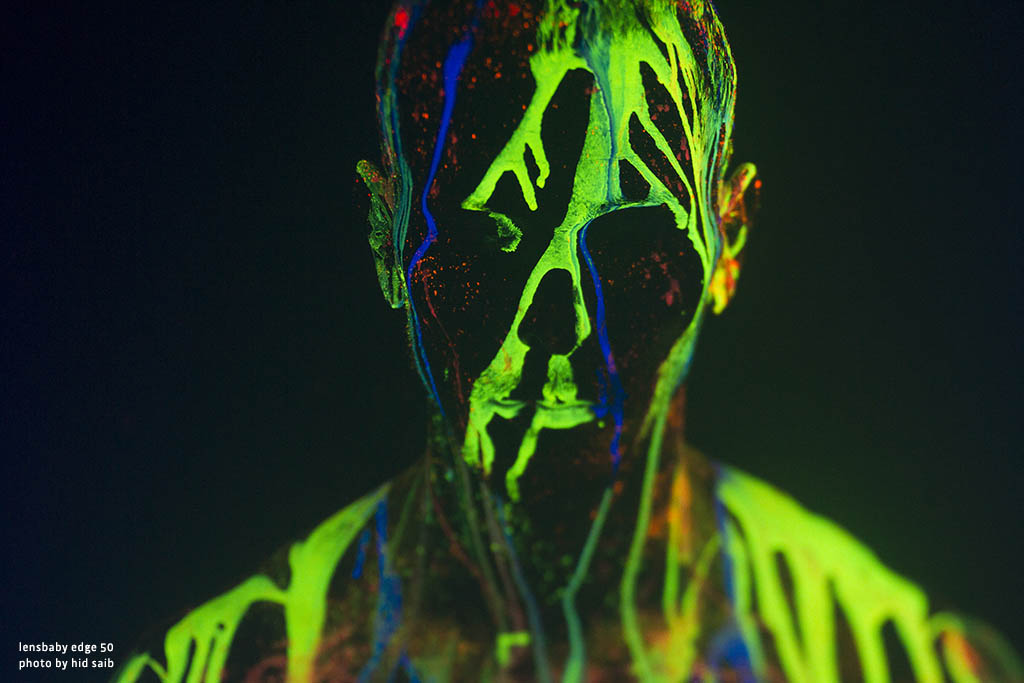 face covered in green yellow neon splashes of paint glow in the dark Lensbaby top 12 photos