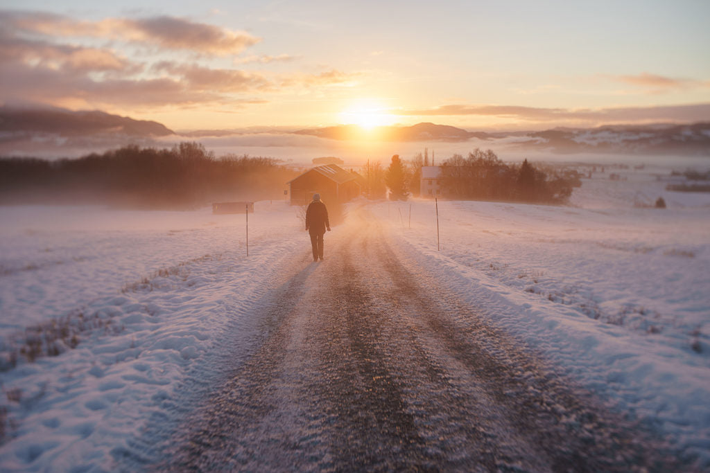Person walking down snowy road during sunset