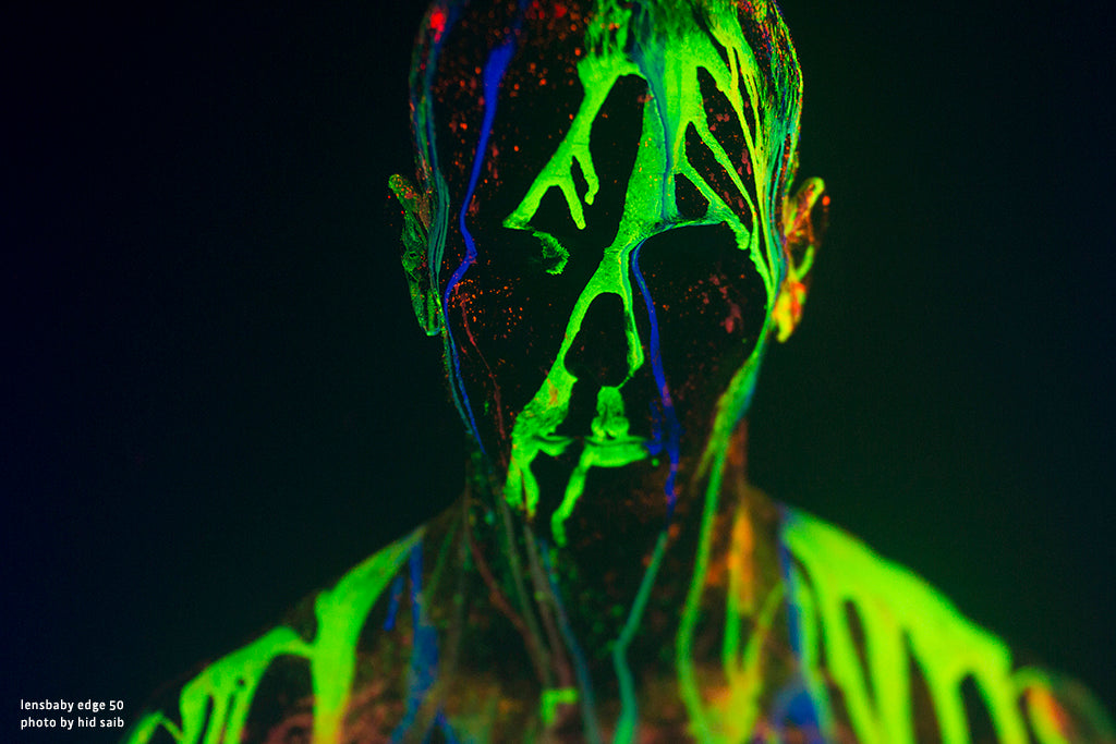 face with glow in the dark paint splashed on it green glowing paint our passion is the imperfect