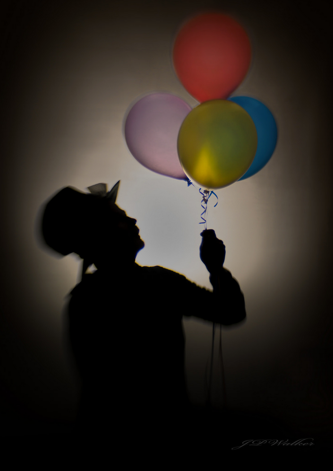 mad hatter clown with bright balloons silhouette bright center Lensbaby featured photos