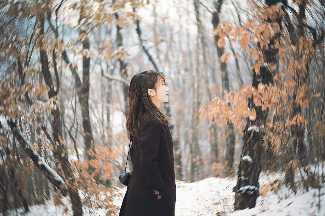 woman with brown hair and bangs eyes closed in snowy winter landscape trees with dead leaves camera lensbaby featured photos