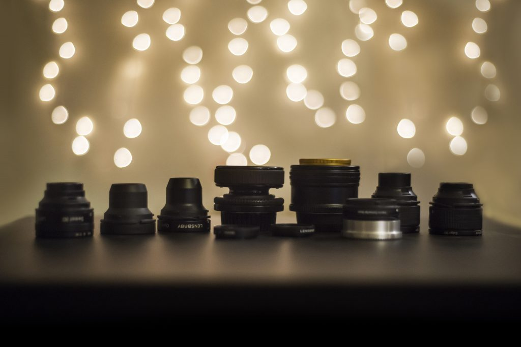 camera lenses Lensbaby lined up on a table in front o f bright lights bokeh Stephanie DeFranco Lensbaby Makers