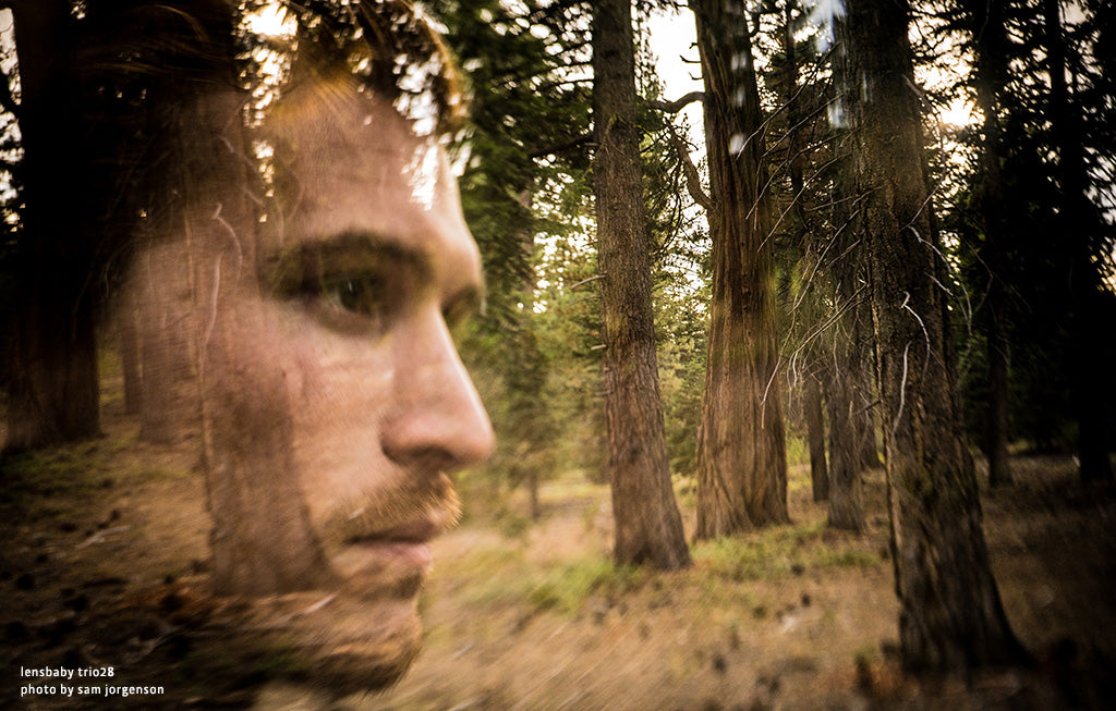 man in woods forest trees green moss serious face lensbaby manifesto discovery is our joy