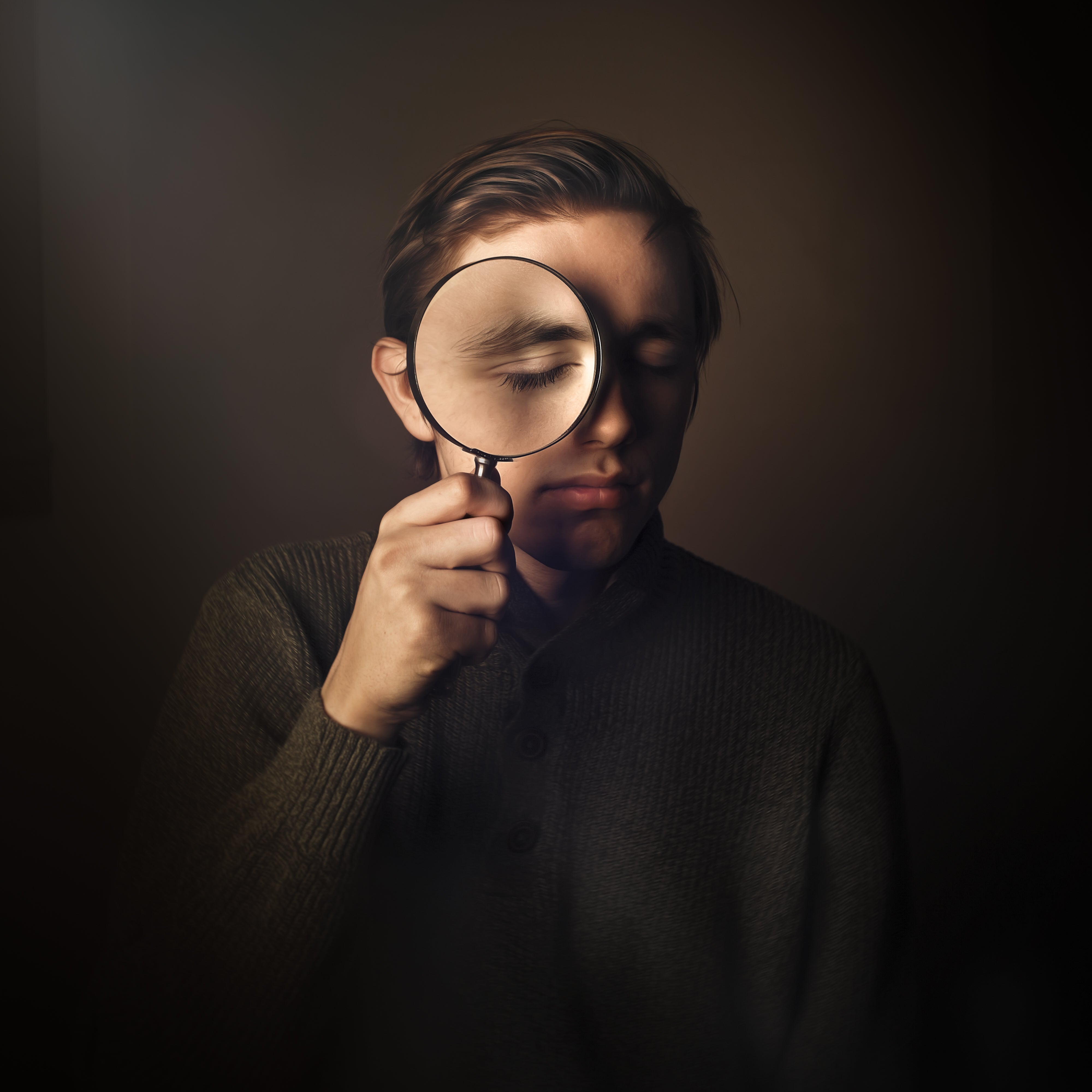 boy with brown sweater and brown hair presses a magnifying glass against his eye caroline jensen burnside 35