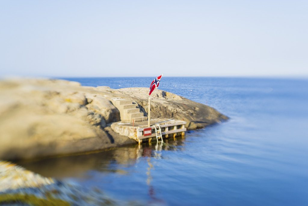Norwegian flag on rocks and water