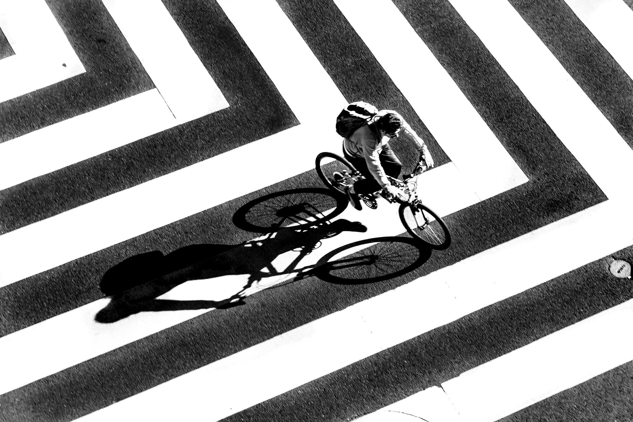 biker crossing a striped crosswalk black and white geometry lensbaby featured photos