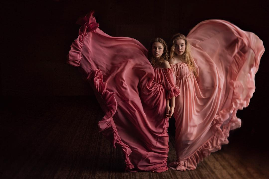 two girls in flowing pink dresses long dresses against black backdrop Lensbaby featured photos Velvet 56