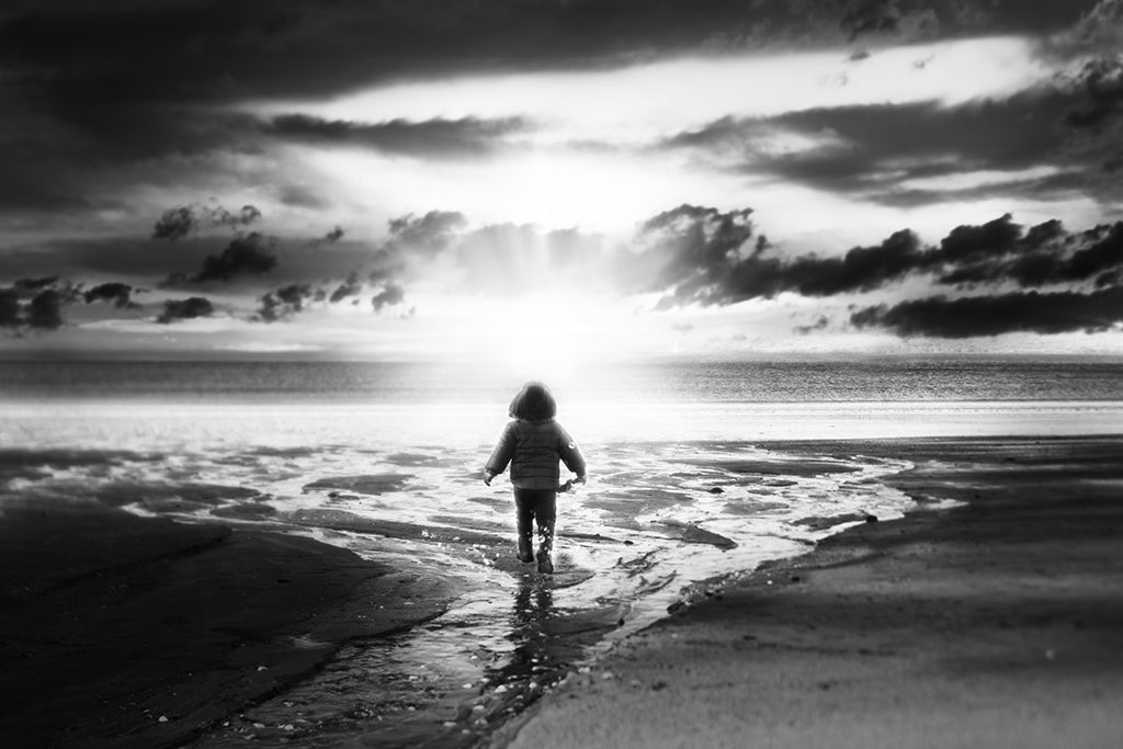 Child at beach in water in front of sun burst and clouds featured photos