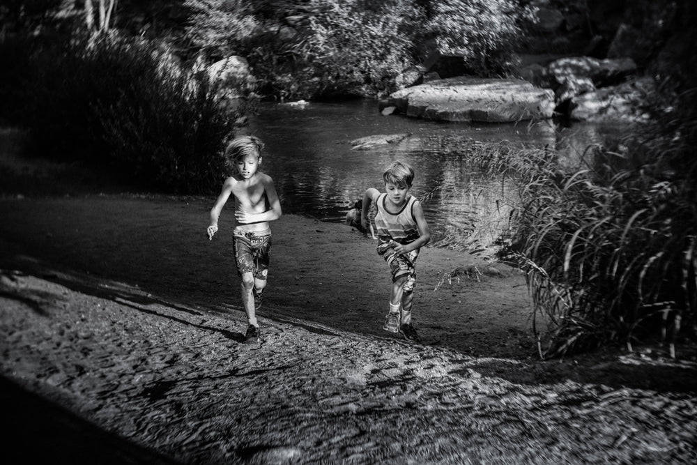 two boys running racing near a lake summer lensbaby journey