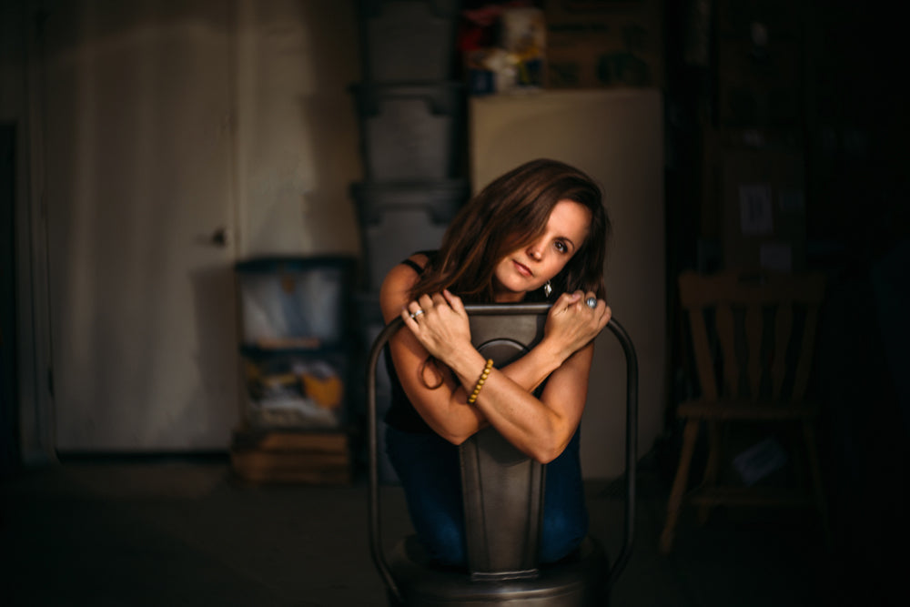 Natalie wheeler portrait woman with brown hair and arms crossed sitting in chair