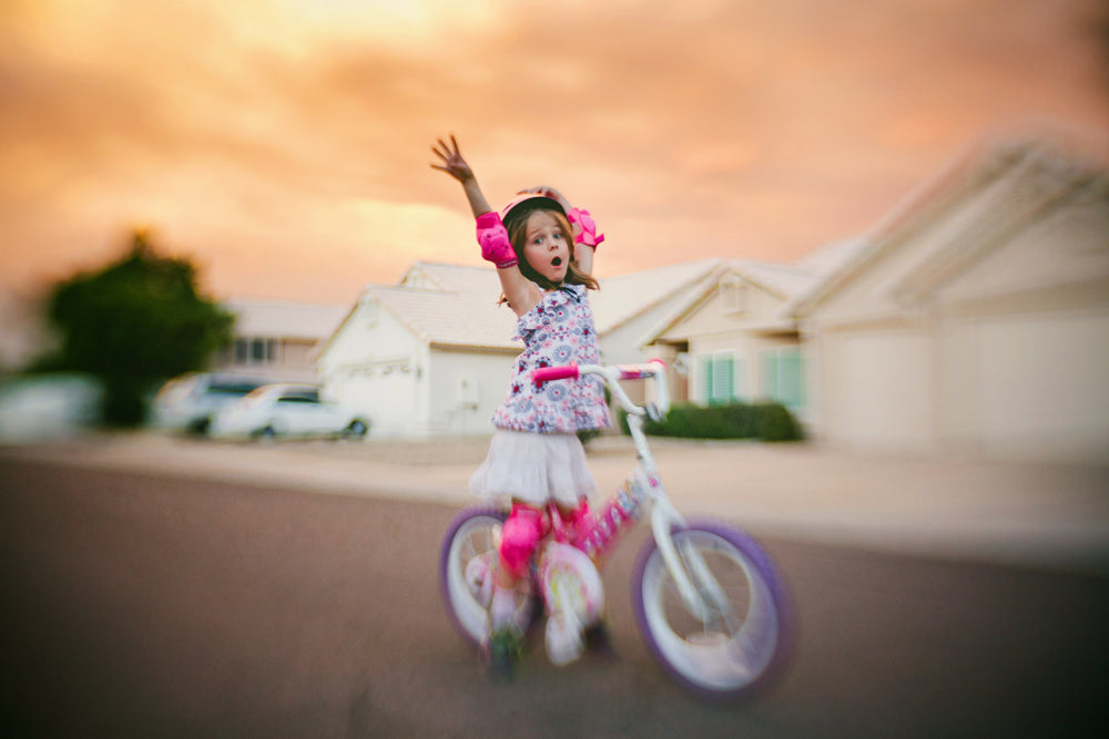 girl in pink on white bike arms up funny face sunset suburbs lensbaby journey