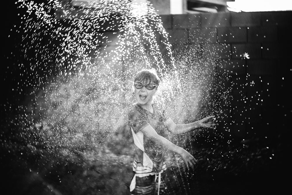 young boy in sprinkler happy wearing swim goggles