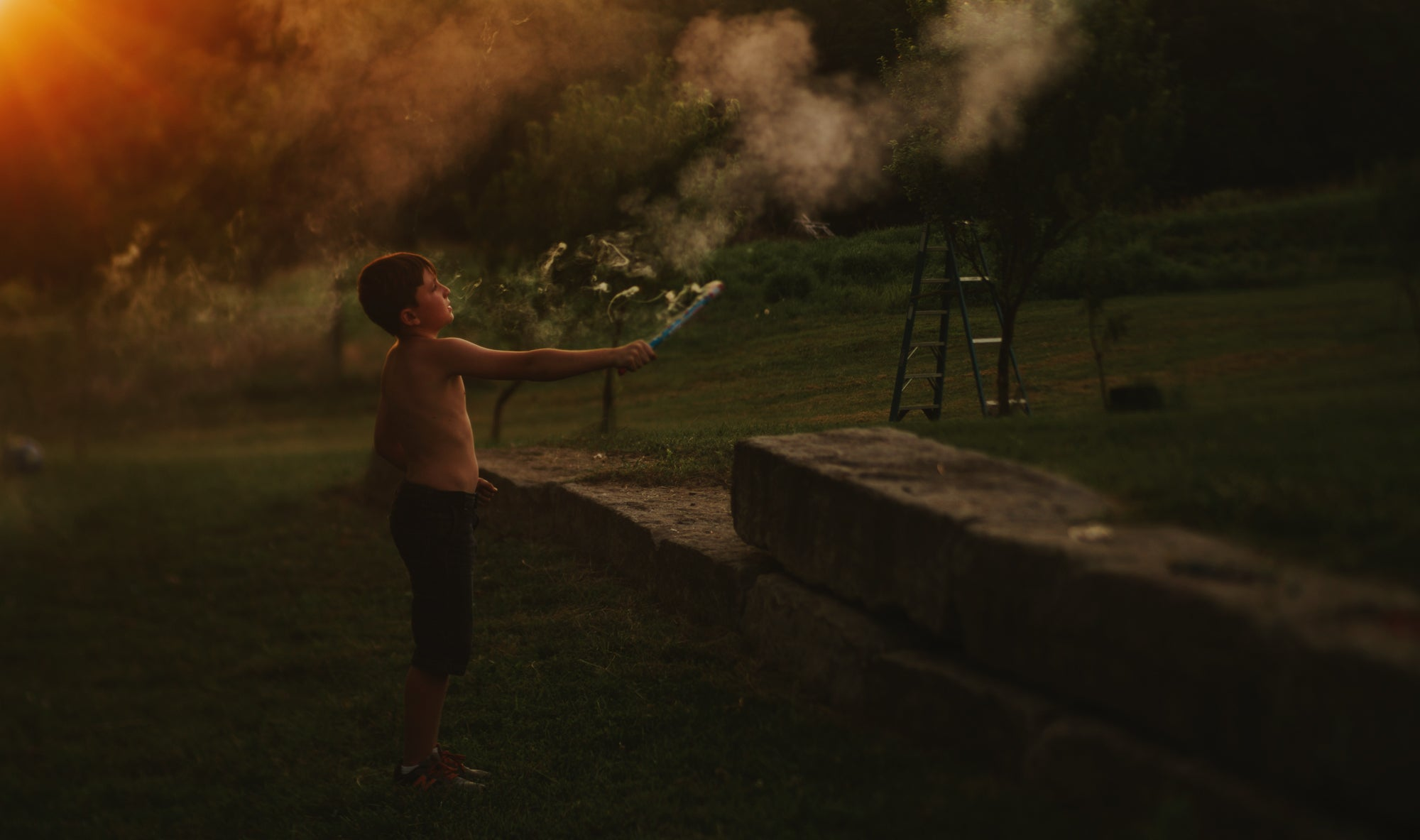 boy with arm extended holding smoking fireworks no shirt summer sunset lensbaby journey story amy cyphers