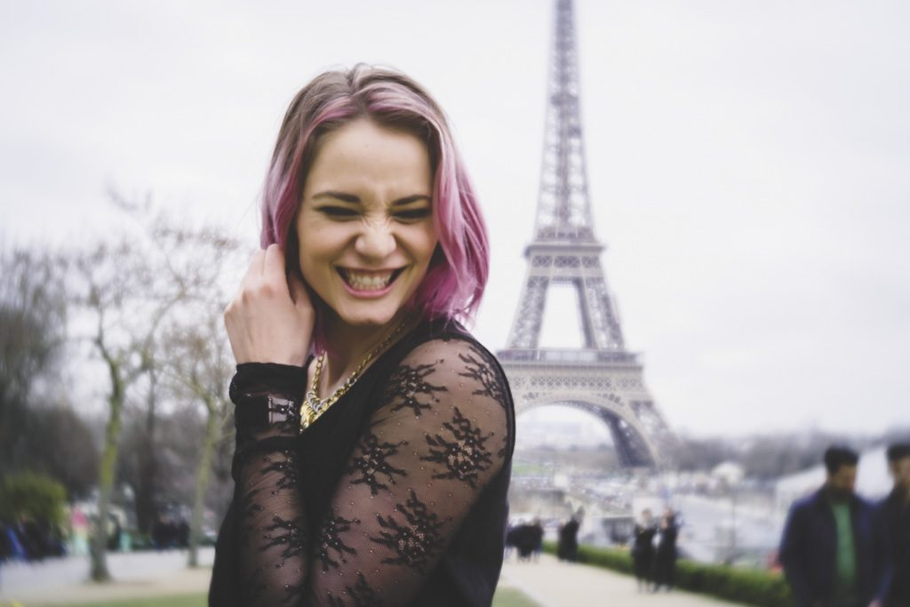 Young woman with pink hair in front of Eiffel Tower Paris