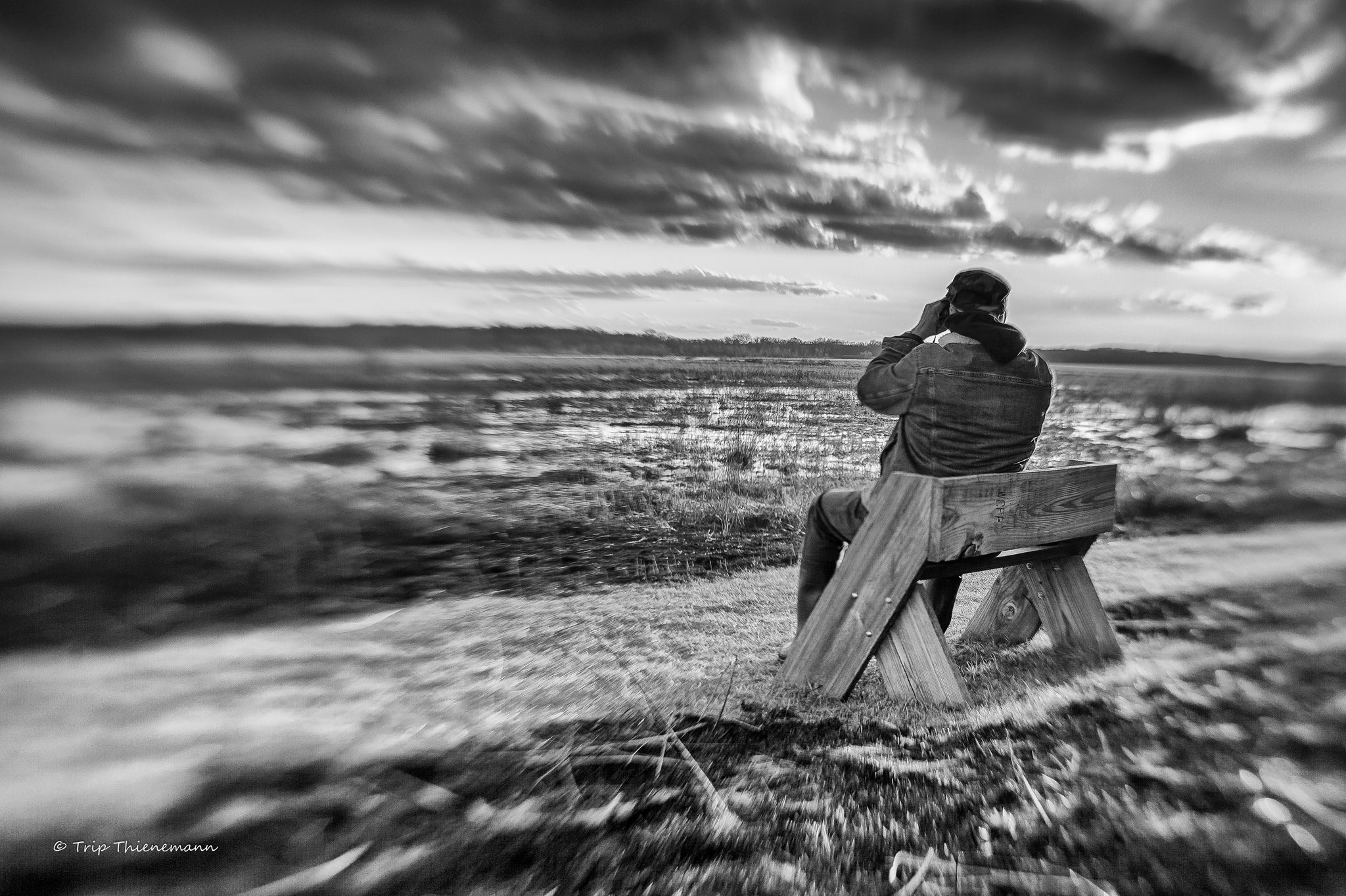 man sitting on a wooden bench looking out at the plains black and white high contrast Lensbaby featured photos