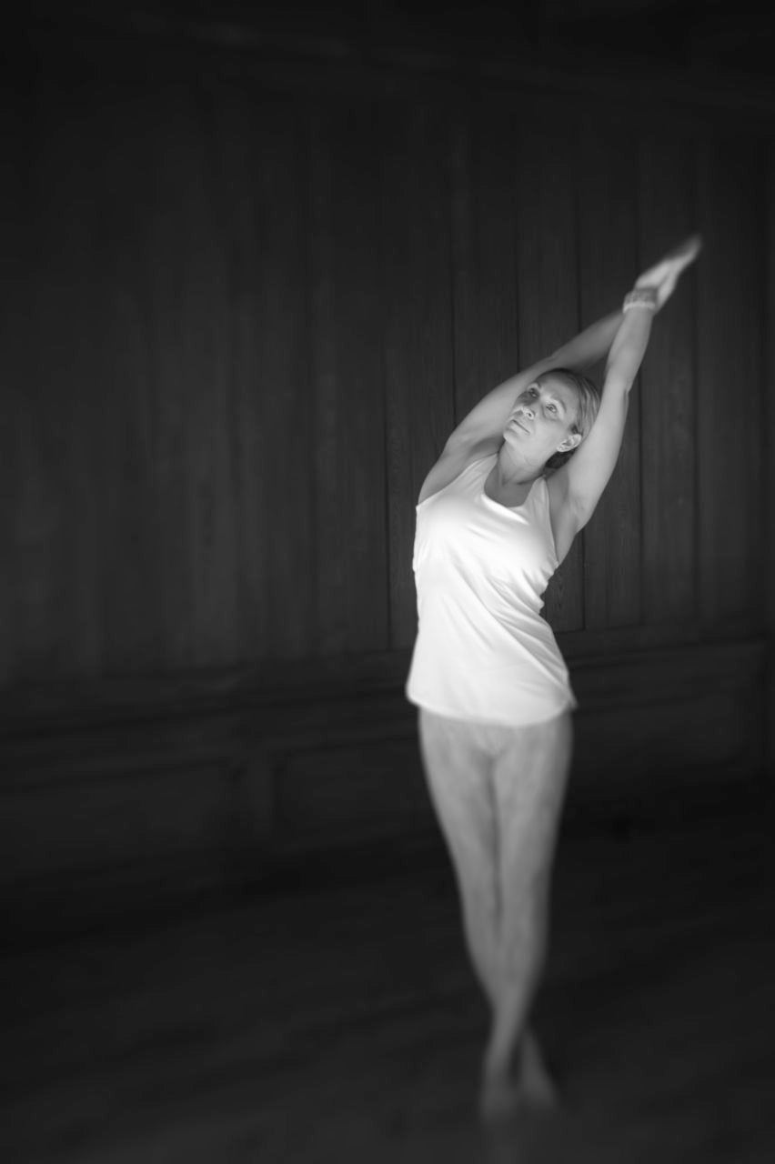 female dancer stretches her arms above her head yoga side stretch white tank top journey story susan currie