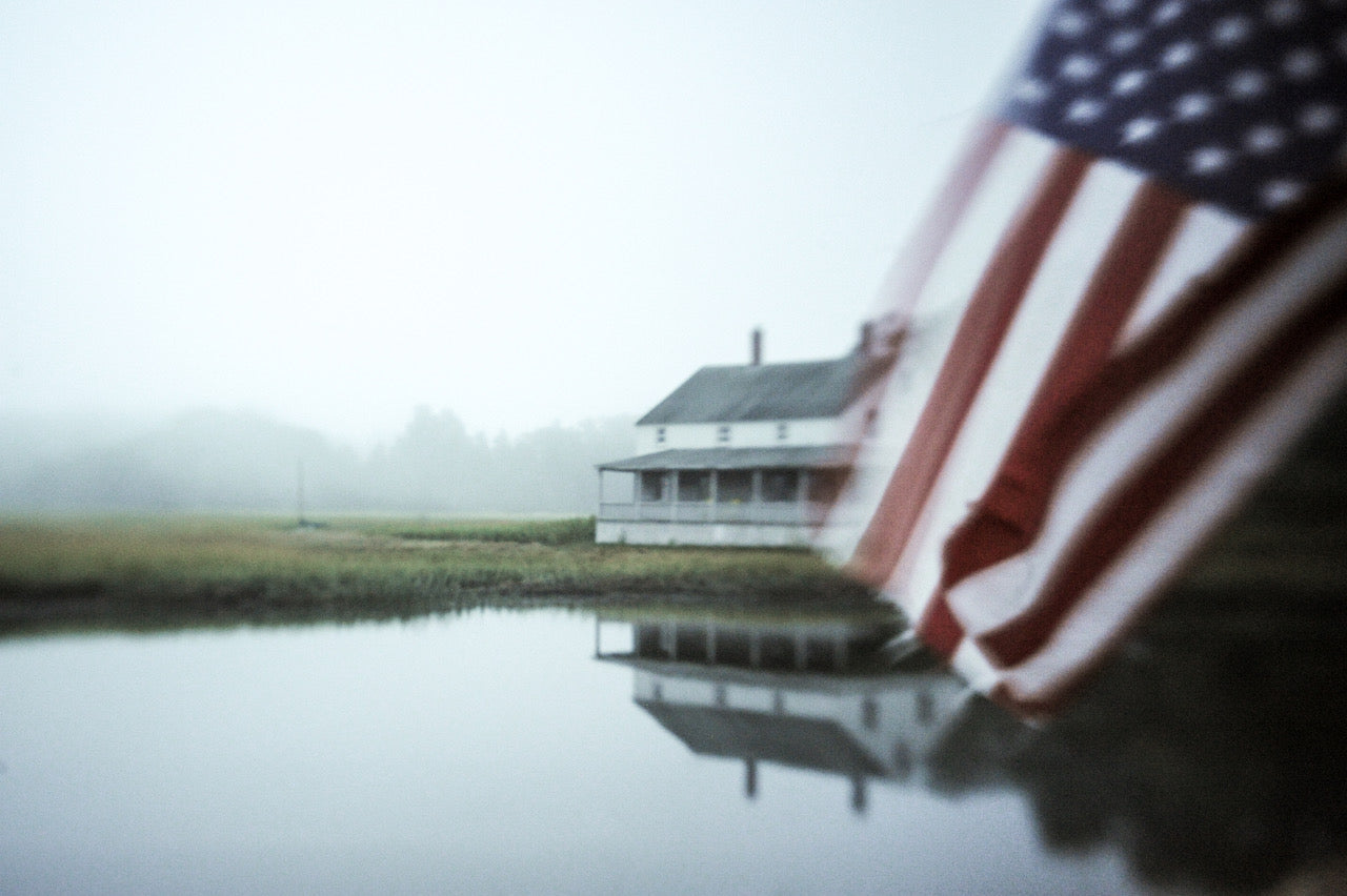big white house on a still lake with an american flag int he foreground misty weather green grass journey story susan currie