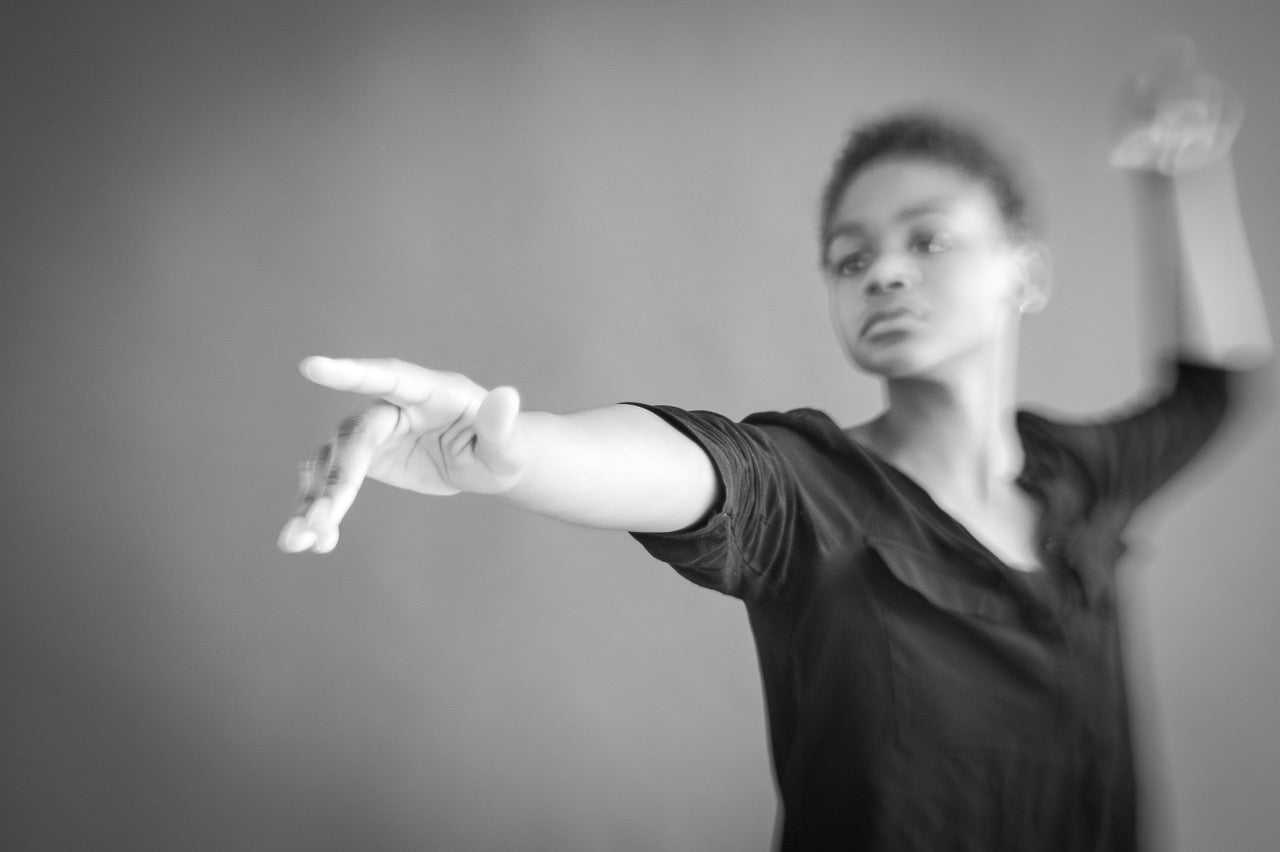 dancer in black tshirt strikes a dramatic pointing pose black and white selective focus photography journey story susan currie