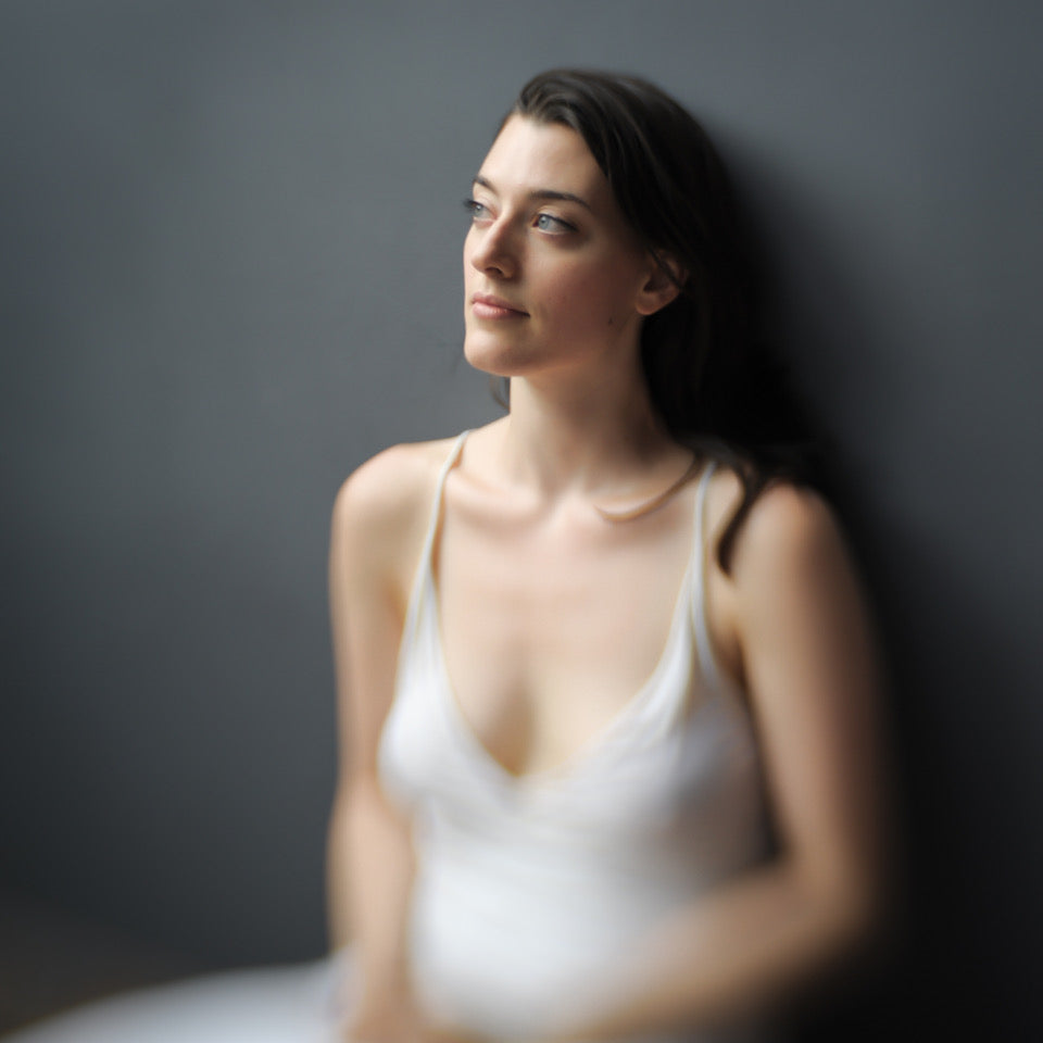 woman in white tank top stares off into space portrait photo collarbone brown hair journey story susan currie