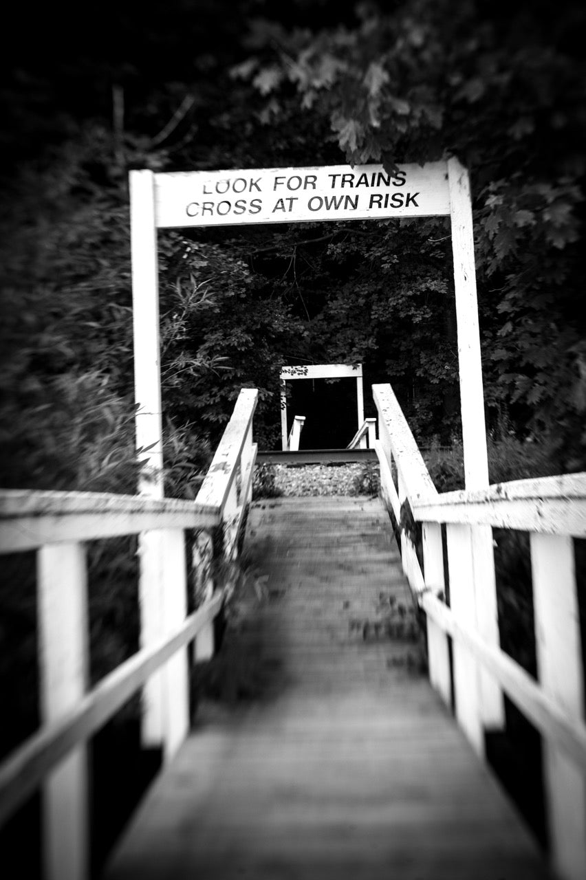 look for trains cross at own risk sign on old rickety stairs going down black and white photo journey story susan currie