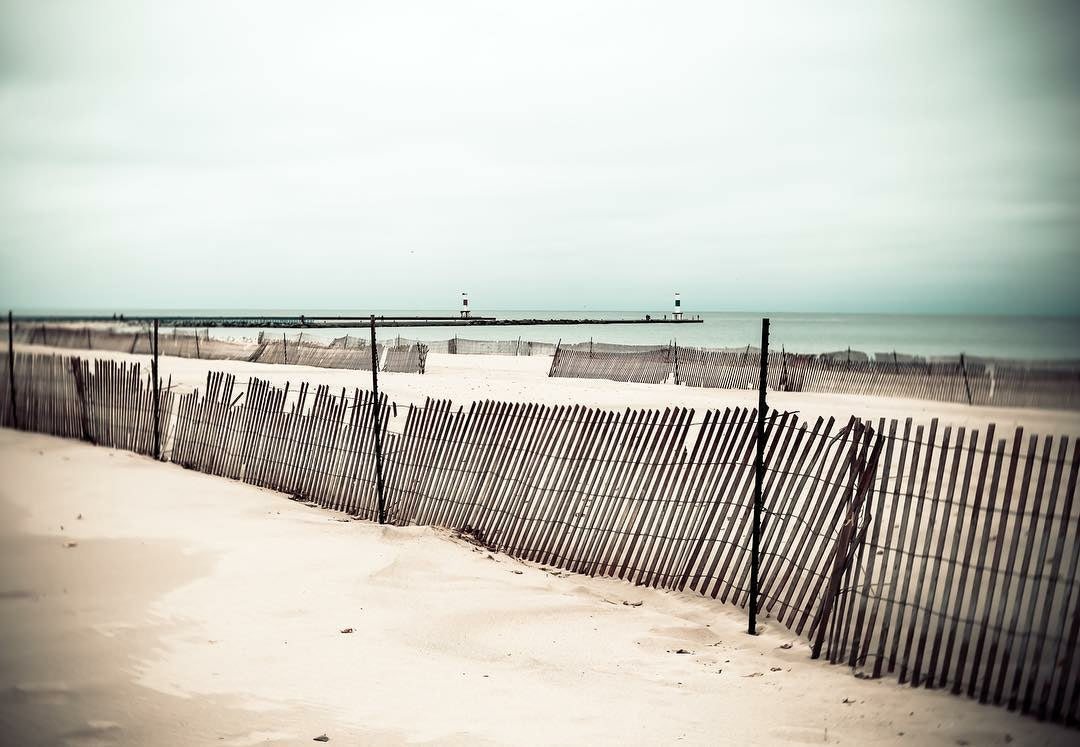 beach with fence falling down green water hazy sky featured photos