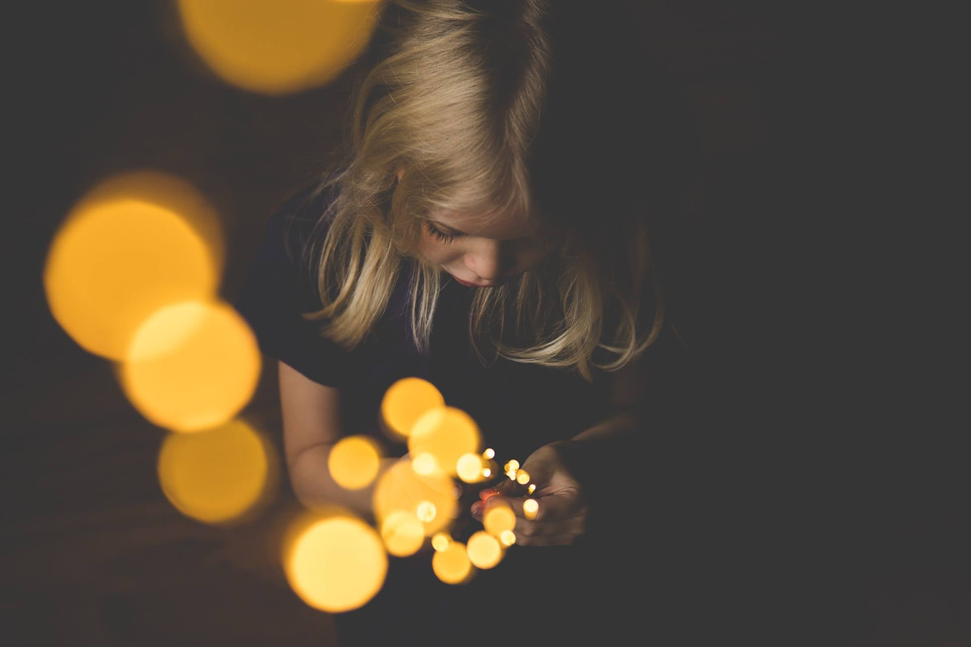 girl with blond hair and yellow glowing lights black background featured photos lensbaby