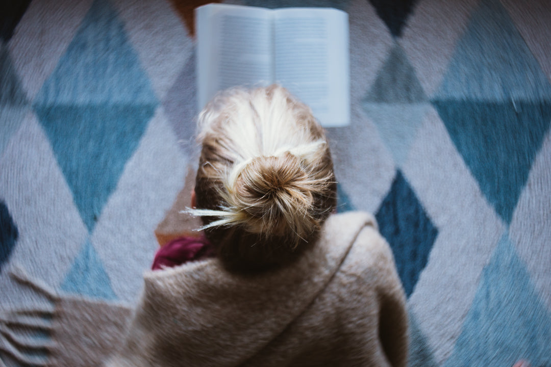 woman with blonde hair tied in a bun reading a book wrapped in a brown sweater looking over her shoulder geometric carpet burnside 35 comparison