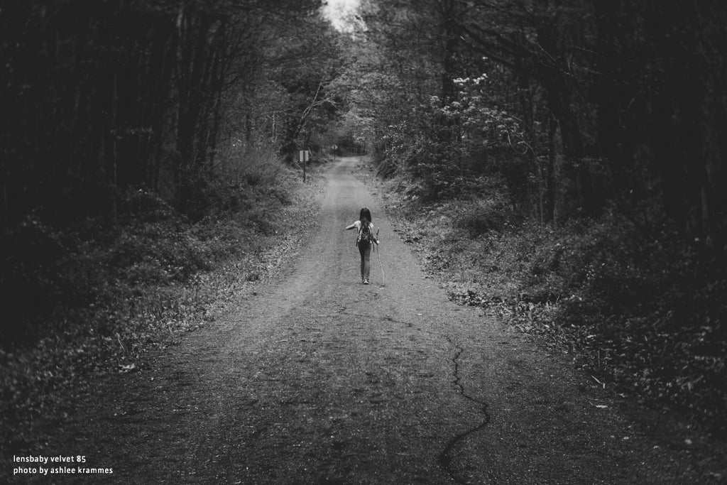 girl walking down path in forest trees dirt road walking stick backpack lensbaby university velvet