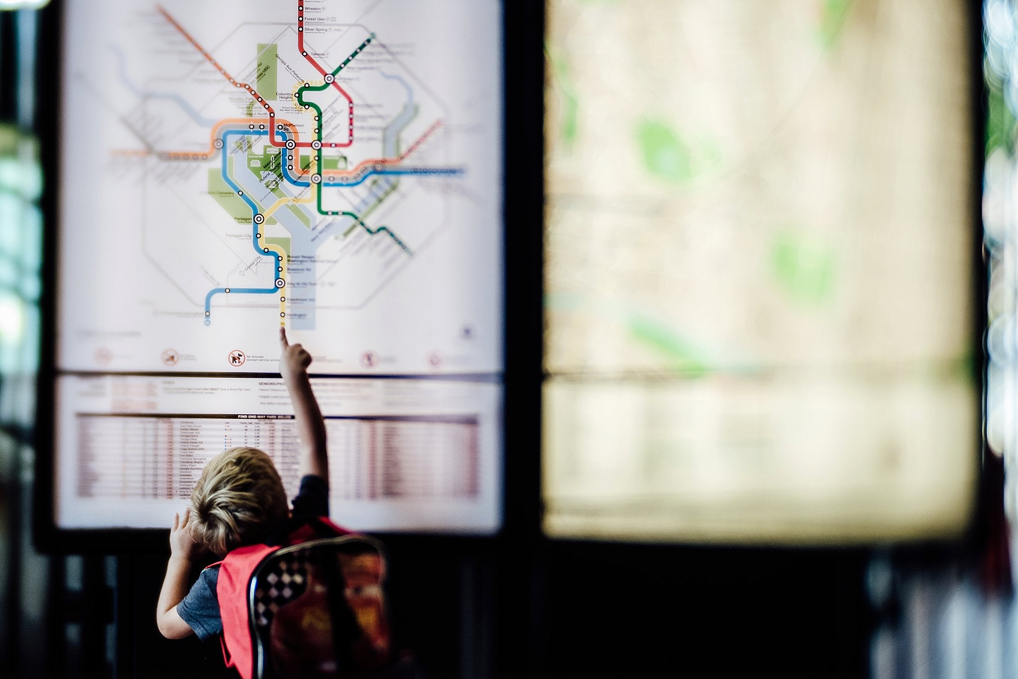 boy looking at a map of the Washington DC metro pointing big red backpack Chelsea Lyn Lensbaby Challenge