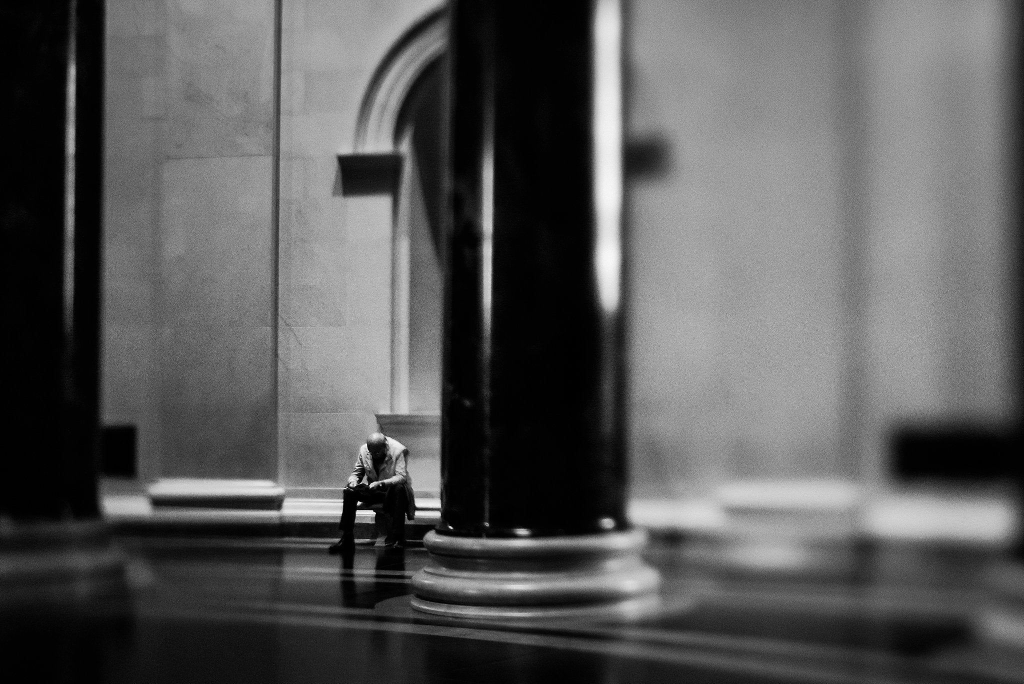 bald man sitting in a hall with pillars and high ceilings black and white shadows stone building Chelsea Lyn Lensbaby Challenge