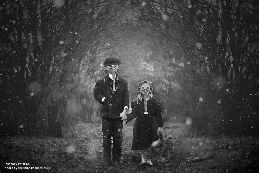 two children holding hands wearing elephant gas masks surrounded by a swirling forest black and white Lensbaby top 12 photos