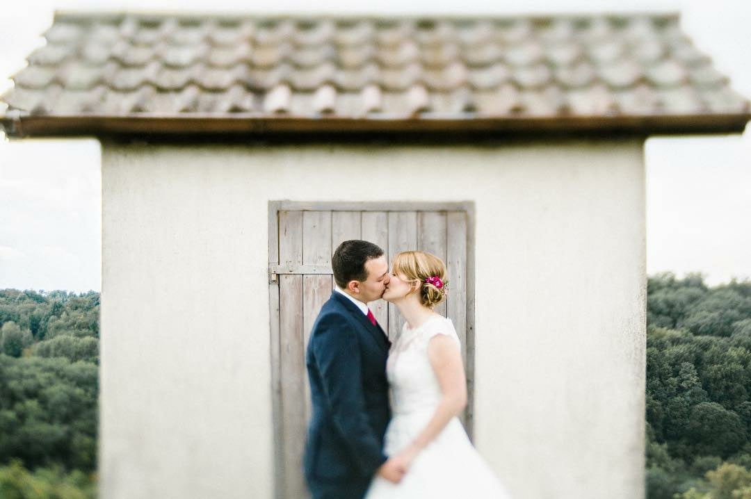 wedding couple bride groom kissing in front of white building featured photos