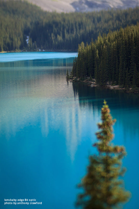 Lake Moraine evening shot with Lensbaby Composer Pro with Edge 80 Optic. Tilt shift effect photography using a slice of focus and vivid colors of the blue lake and bright green evergreen firs.