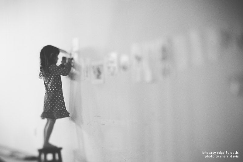 Kindergartener in a polka dot dress hanging up classroom art in black and white with tilt shift effect by the Edge 80 Optic from Sherri Davis.