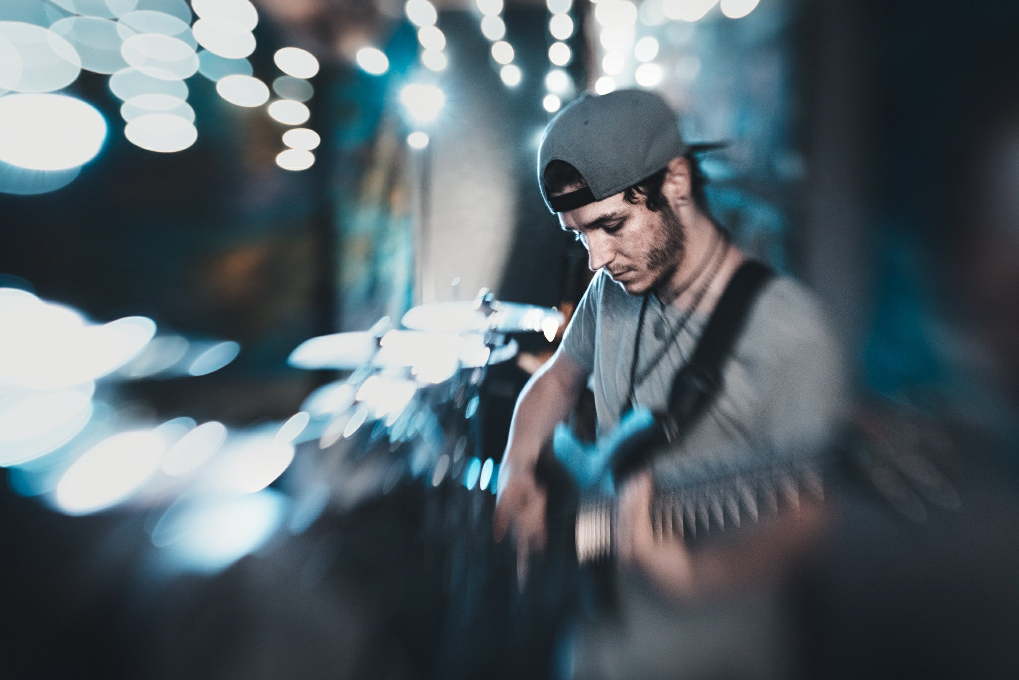 musician concert guitarist man with guitar on stage backwards hat beard selective focus blue lights Lensbaby featured photos